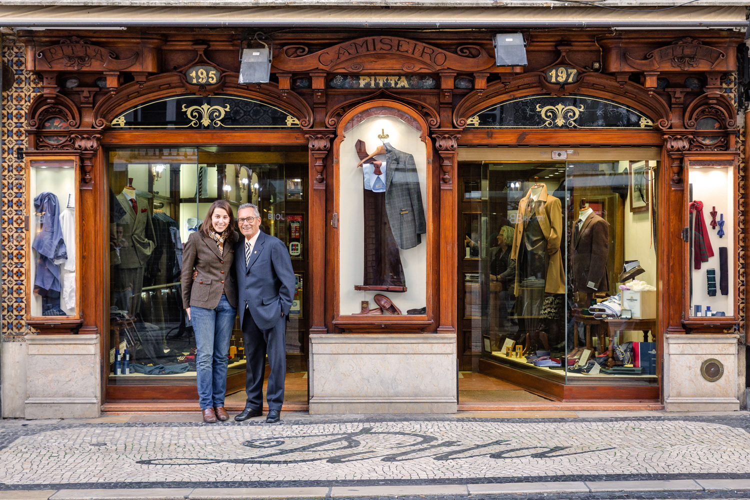 Cláudia Marques and her grandfather Alfredo Teixeira welcome visitors into their men's clothing store