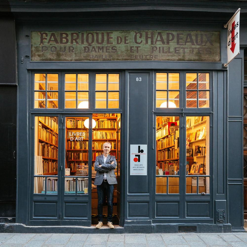 Stefan Perrier, delante de lo que parece una tienda de sombreros, pero que en realidad es una famosa librería de arte