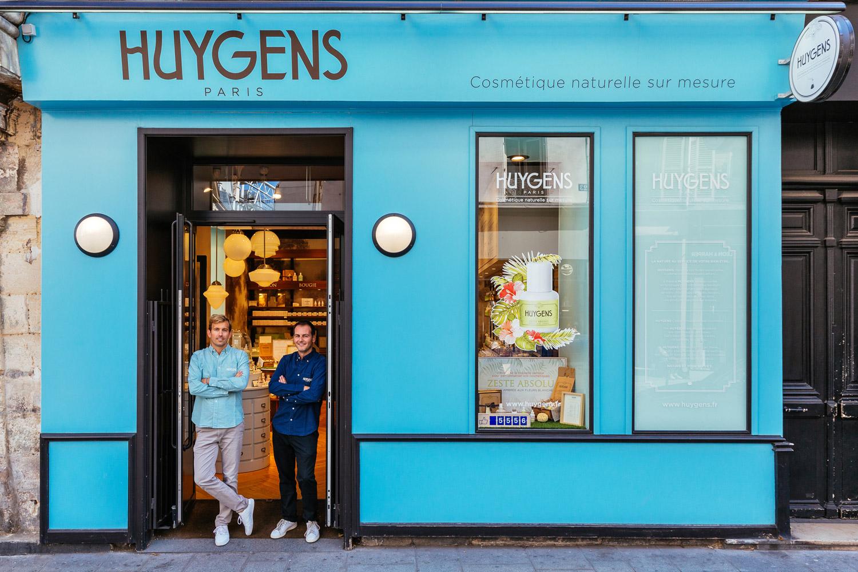 Daan Sins (sinistra) e Sébastien Guerra danno il benvenuto con un sorriso ai clienti del loro negozio di prodotti cosmetici