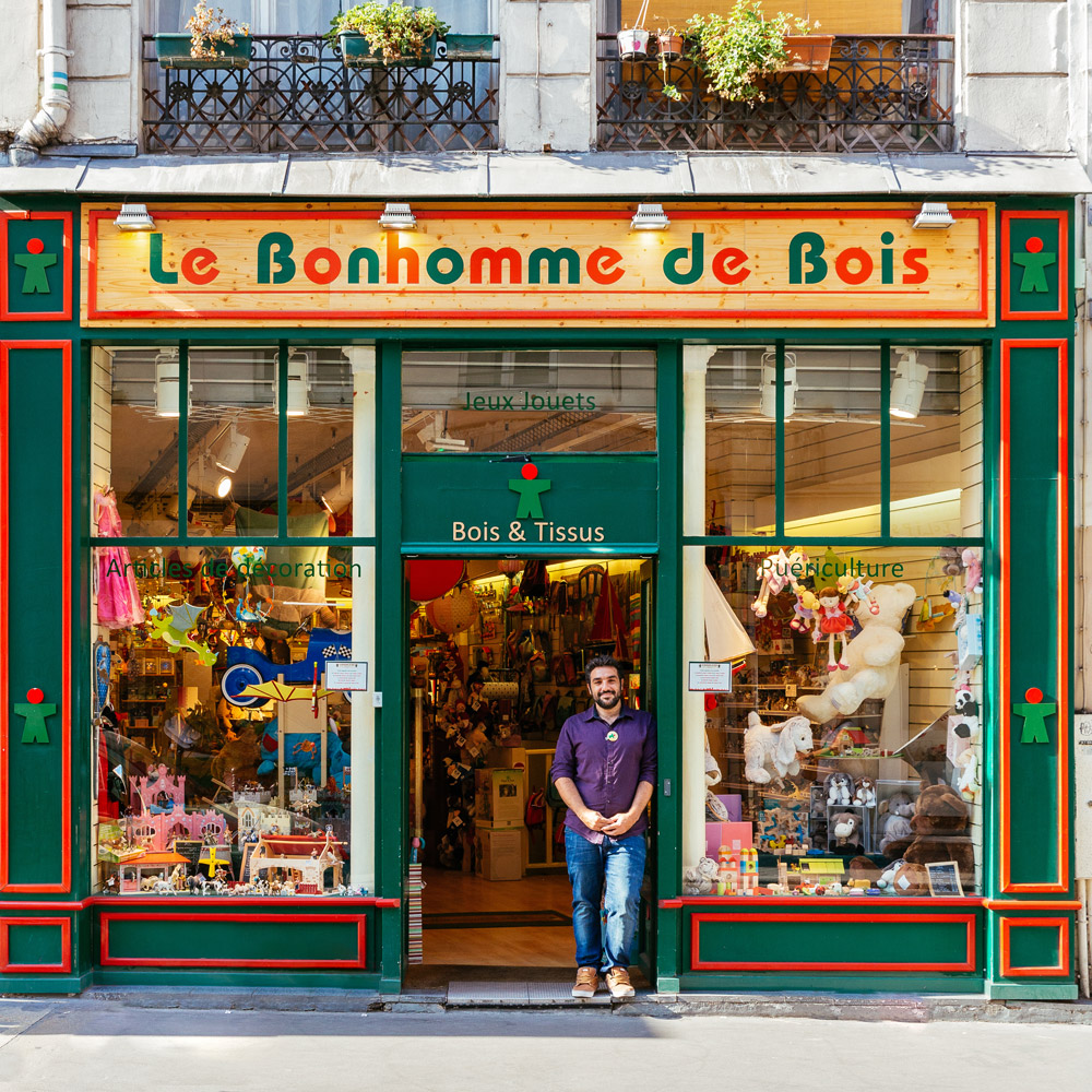 Yann Bilhaud waits for children at the door of the toy shop he runs