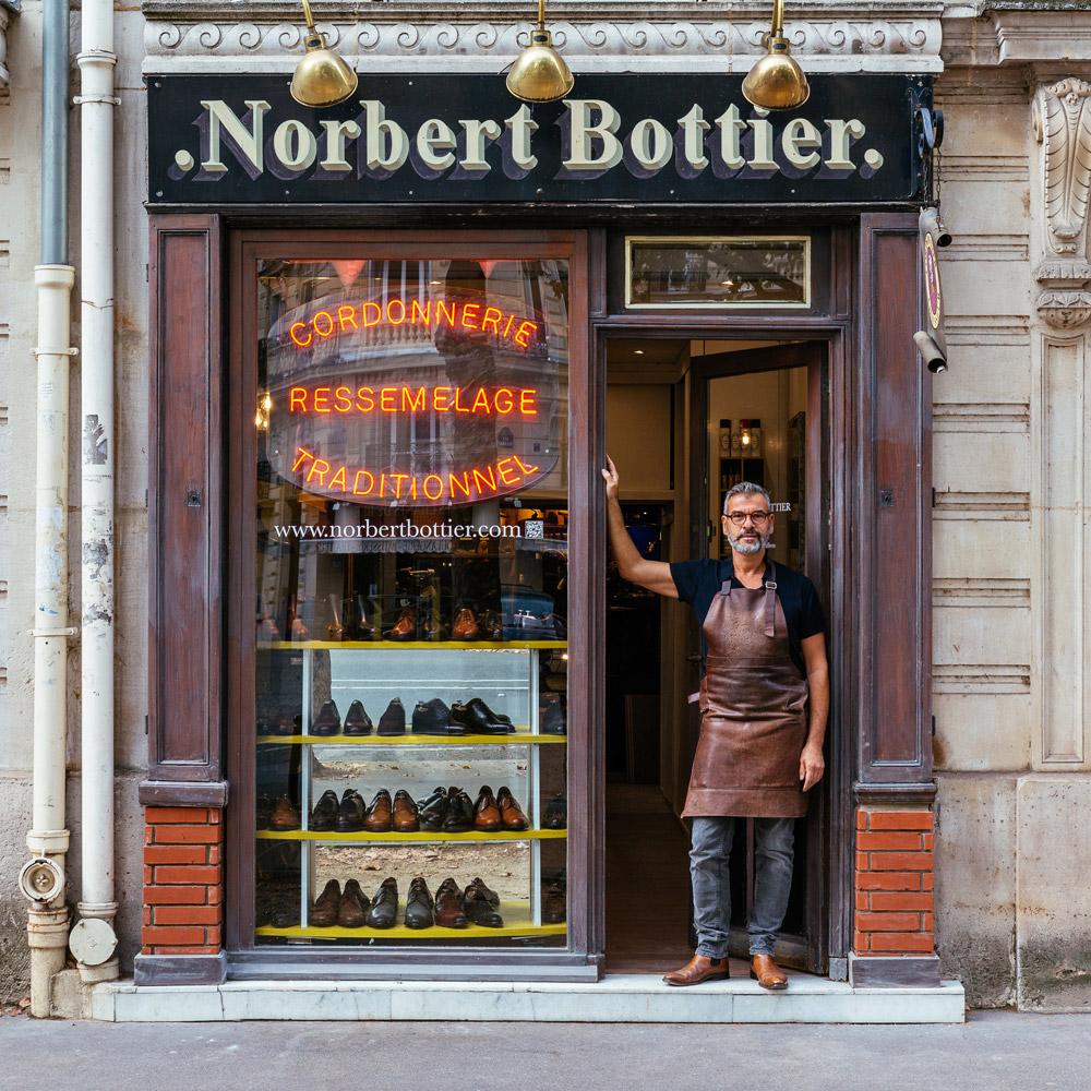 Norbert montrant fièrement la collection de chaussures qu'il crée.